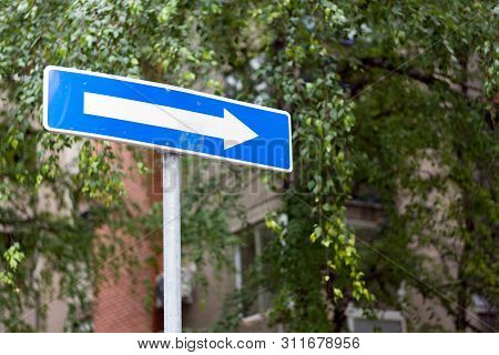Right Direction Allowed One Way Blue Street Sign On A City Street, Against The Gray Buildings And Cl