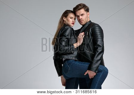 Tough young man embracing and protecting his girlfriend while holding her leg, both wearing leather jackets and jeans, standing on gray studio background
