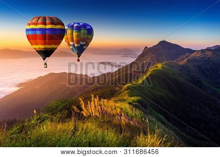 Landscape Of Morning Fog And Mountains With Hot Air Balloons At Sunrise.