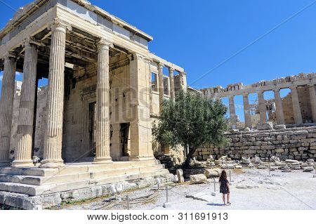 A young woman walking by herself admiring the glorious ancient Greek Old Temple of Athena atop the Acropolis, in Athens, Greece with the Parthenon and an olive tree in the background. poster