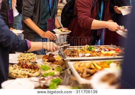 Close Up Of People Serving Themselves With Canapes In Buffet Of Restaurant.