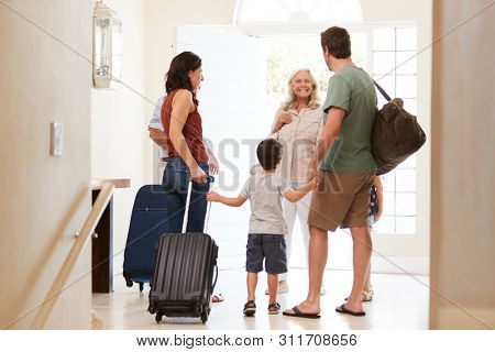Three generation white family leaving their home to go on holiday, full length, back view