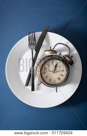 concept of intermittent fasting, ketogenic diet, weight loss. alarmclock fork and knife on a plate