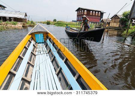 Maing Thauk, Myanmar - April 2019: Traditional Burmese Wooden Boat Going Through Maing Thauk Village