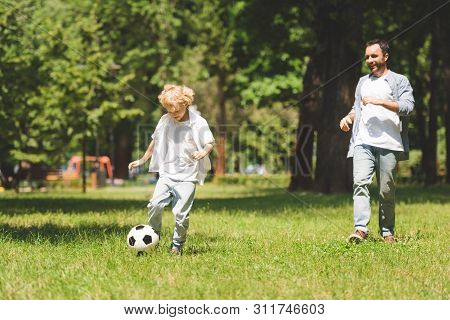 Father And Adorable Son Playing Football In Park During Daytime
