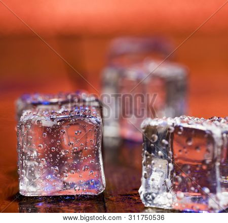 Melting Ice Cubes With Droplets Of Water On A Wooden Background.