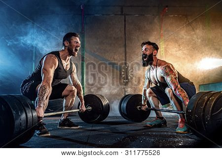Two Muscular Bearded Tattoed Athletes Training, Lifting Heavy Weight Bar In Smoke At Gym. Scream. Wo