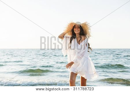Photo of young brunette woman in beach dress and straw hat walking by seaside in summer morning