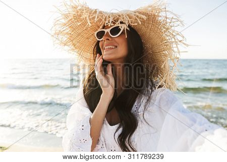 Photo of joyful brunette woman in beach dress and straw hat smiling while walking by seaside in summer morning