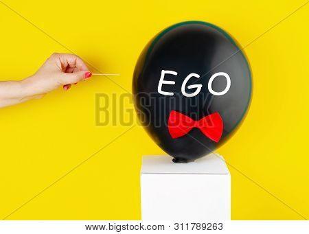 Black Balloon With The Text Ego Over It And Woman Hand That Is Going To Pop Up Balloon With Needle.