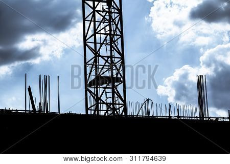 Dark Cloudy Sky At Building Construction Site Silhouette Crane. Investment Business Activity In Soci