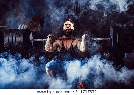 Muscular Bearded Tattoed Fitness Man Doing Deadlift A Barbell Over His Head In Modern Fitness Center