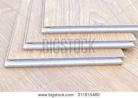 Laminate Floor Planks And Tools On Wooden Background. Different Carpenter Tools On The Laminated Flo