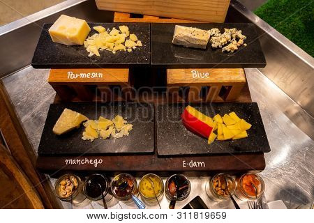 Variety of cheese on black stone plate in buffet line
