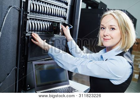 Cloud storage service. female engineer replacing hard drive in server