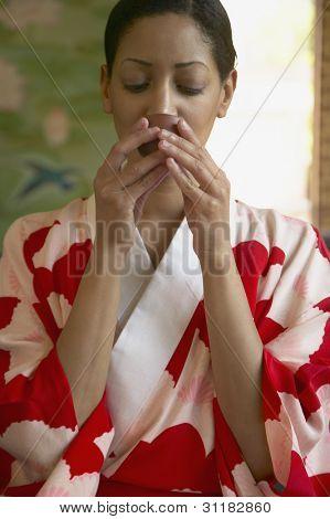 Woman in kimono drinking tea