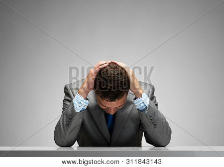 Frustrated Man Sitting At Desk With Hands On Head. Businessman Stressed From Pressure At Work. Unemp