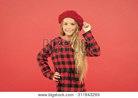 Kid Little Cute Girl With Long Blonde Hair Posing In Beret Hat And Checkered Dress Red Background. F