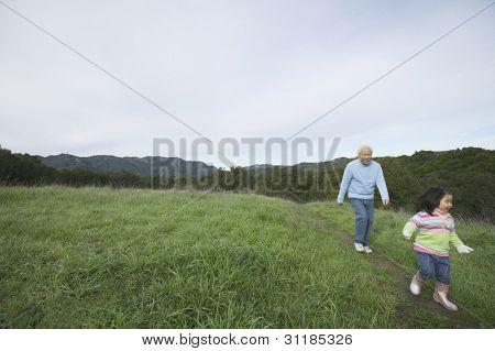 Senior man and granddaughter walking together