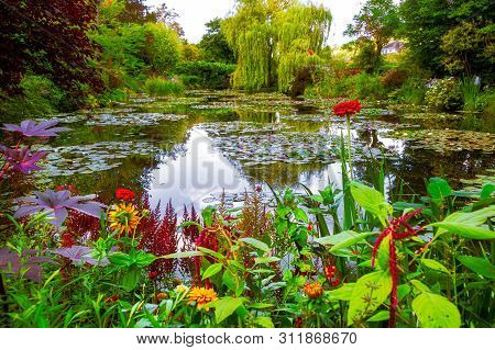 Monet garden and pond at Giverny, France. Beautiful garden and pond with clustered of colorful flowers, variety of trees and shrubs in summer at Giverny. poster