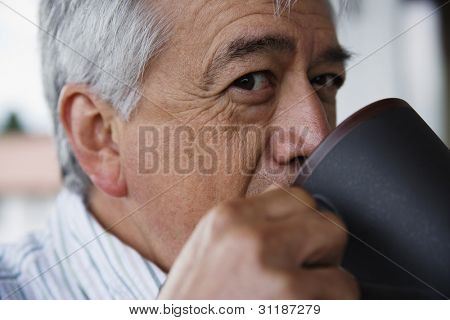 Close up profile of elderly man drinking coffee
