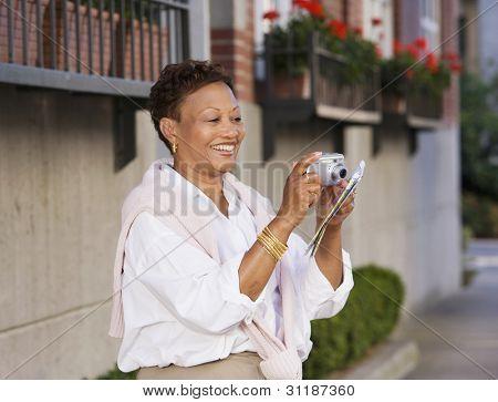 Mature woman taking photograph