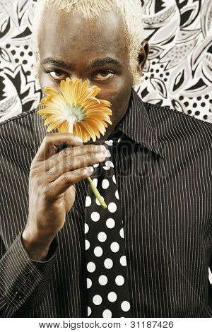 Young man smelling yellow flower