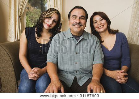 Portrait of Hispanic family on sofa