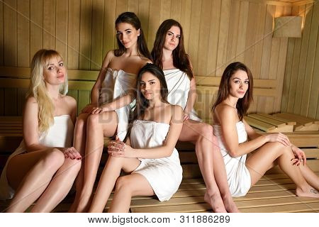 Girls In White Towels Relaxing In The Sauna.