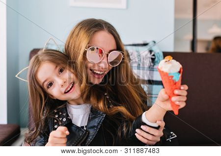 Trendy Laughing Mom In Sunglasses Having Fun With Excited Daughter Indoors. Portrait Of Cute Brunett