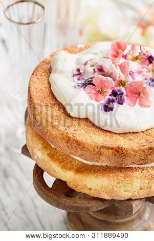 Victoria Sponge Cake With Whipped Cream And Sugared Flowers Over A White Wooden Rustic Table Top.