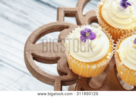 Beautiful Vanilla Cupcakes With Buttercream Icing Decorated With Sugar Coated Violet Flowers. Select