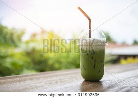 Iced Green Tea In Plastic Cup / Matcha Green Tea Latte Frappe And Straw On Wooden Table With Nature
