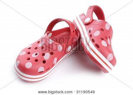 Young girls red summer shoes with spots on a white background.