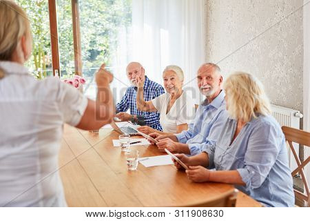 Group of seniors at computer class with tablet computer and laptop in retirement home