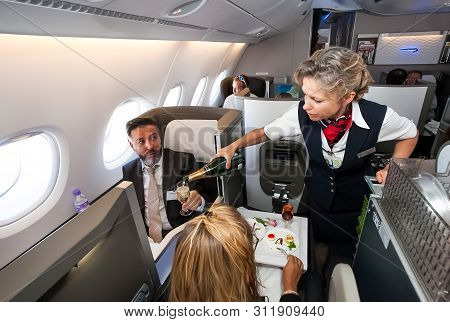 Johannesburg, South Africa - February 06 2014: Female Cabin Crew Pouring A Glass Of Champaign In Bus