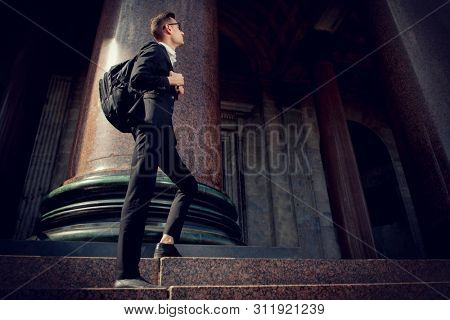 A full length portrait of a goodlooking young student walking in the street. Men's formal fashion, success, education.
