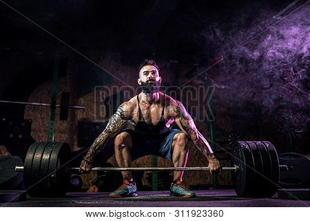 Muscular Fitness Man Doing Deadlift Of A Barbell In Modern Fitness Center In Smoke. Functional Train