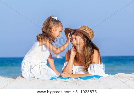 daughter putting sun lotion on mothers face