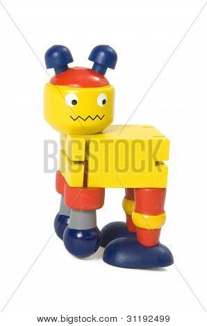 Wooden toy robot bending forward on a white background.