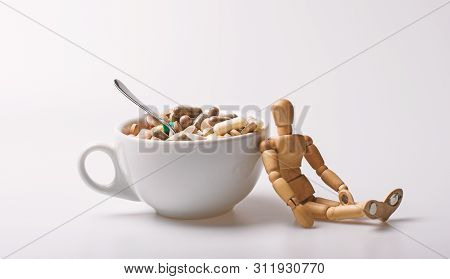 Wooden Human Dummy Near Cup Full Pills And Tablets. Vitamin Cocktail. Health Problem. Immunity Care
