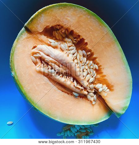Orange Halved Melon With Seeds, In A Shady Blue Bowl Background
