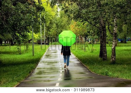 Young Beautiful Girl Walking Alone Under Green Umbrella In The City Park In Summertime