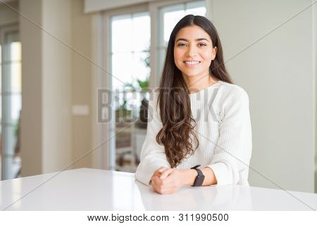 Young beautiful woman at home on white table with a happy and cool smile on face. Lucky person.