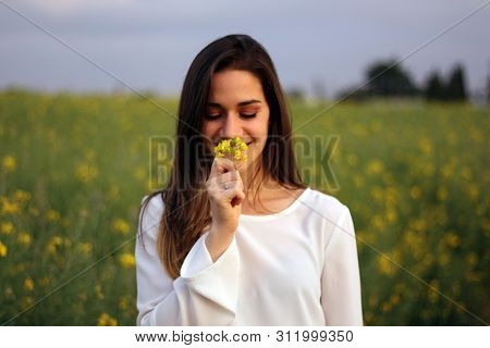 Women Smelling Yellow Flower In Yellow Flowers Field With Copy Space