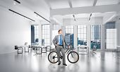 Smiling man in business suit standing with bike at design studio with computer workstations. Happy businessman with bicycle at modern office interior with panoramic windows, desks and chairs poster