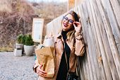 Cute young woman with glasses and red lips leaned on the fence holding foodstuffs from the store. Charming girl in stylish coat  returnes from supermarket with full bag of tasty meal. poster