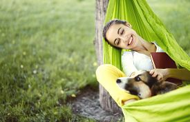 Smiling Young Woman In Green Hammock With Cute Dog Welsh Corgi In A Park Outdoors. Beautiful Happy F