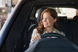 Mature beautiful woman sitting in car looking away while trying new automobile. Portrait of daydreaming mature woman doing drive test of new car. Cheerful smiling lady enjoying driving.