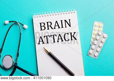 Brain Attack Written In A White Notepad Near A Stethoscope, Pens And Pills On A Light Blue Backgroun